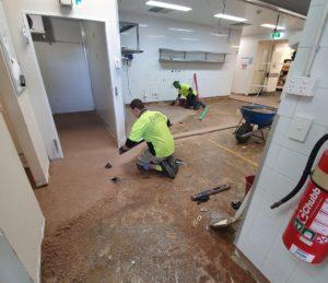 2 workers screeding a floor